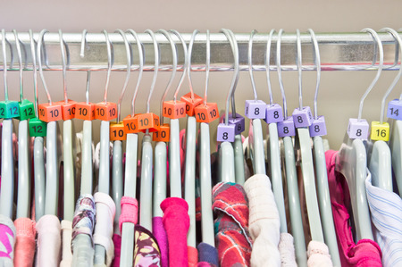 clothing shop: Casual tops on hangers in a charity store
