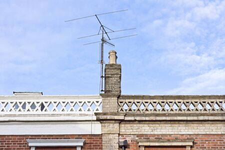 airwaves: Chimney on the top of a victorian building in the UK with a television antenna