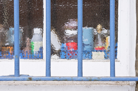 frosted window: Blue bars over a frosted window with household items Stock Photo