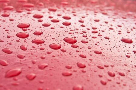 red metal: Numerous drops of fresh rain on a red metal surface Stock Photo