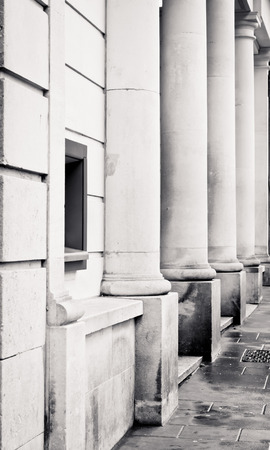 ouside: Row of stone pillars on the ouside of an urban building with a cash dispenser Stock Photo