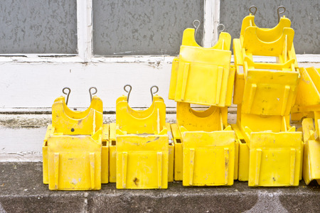 ledge: Yellow pastic clips used for scaffolding, on an exterior window ledge
