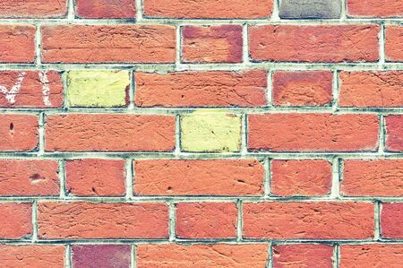 conspicuous: Two yellow painted bricks in a red brick wall Stock Photo