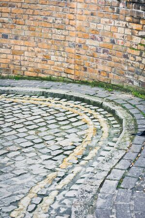 curving lines: Double yellow lines on a curving cobbled street
