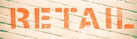 commercialism: Retail written in orange ink on a brick wall
