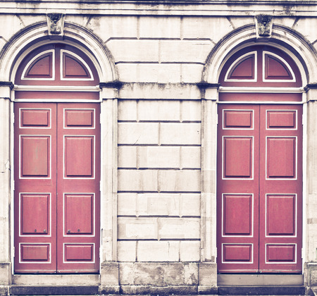 large doors: Two red arched doors in a large stone wall