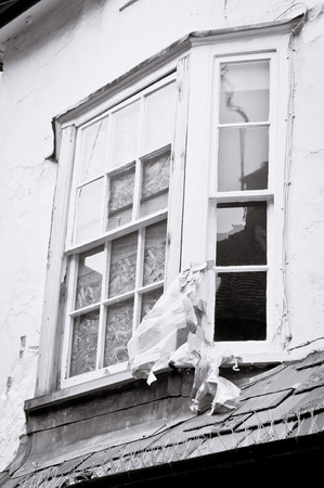 A window in an old house boarded up