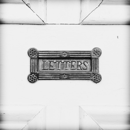 english house: An antique letterbox on a wooden front door of an english house