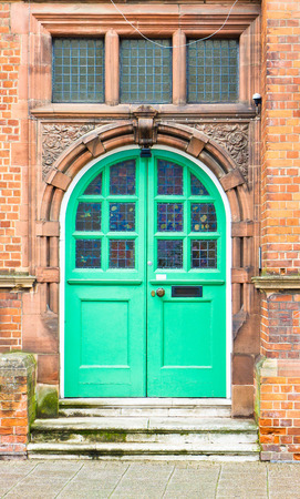 public address: A green double arched door in a red brick building in the UK