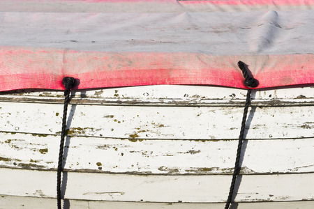 Edge of a weathered wooden boat with a protective cover