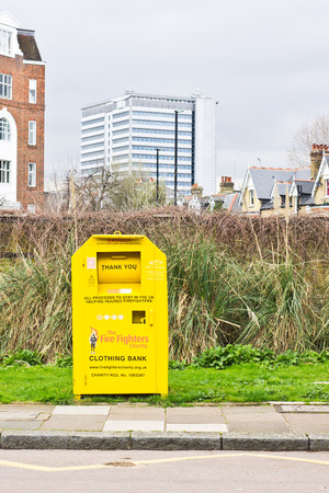 secondhand: CHISWICK, LONDON, UK - APRIL 4 2015: A yellow clothing bank for the firefighters charity by the edge of a road in the Chiswick area of London Editorial