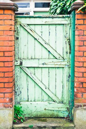 garden gate: A weathered wooden garden gate in a red brick wall in the UK