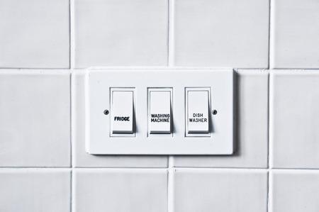 the switch: Interruttori per apparecchi in casa contro una parete piastrellata