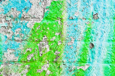 Peeling paint on a weathered brick wall