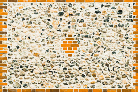 renovated: A renovated flint stone wall with modern red bricks
