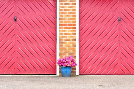 garage doors: Pot of pink flowers in front of red garage doors Stock Photo