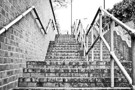 urban decline: Concrete steps with metal railings from a low down perspective