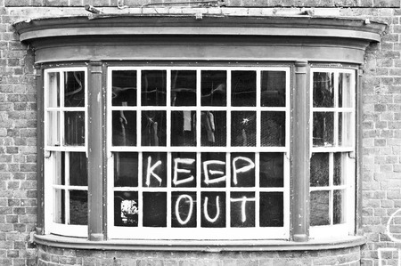 window graffiti: A window in a building for demolition, with warning graffiti