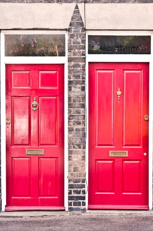 Neighbouring red wooden front doors in neighbouring homes in the UK Stock Photo