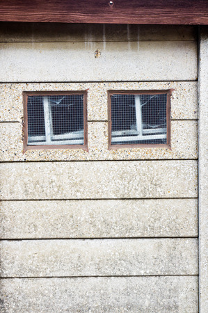 outbuilding: two small square windows in a stone wall Stock Photo