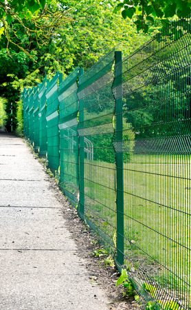 trespasser: A high green wire fence next to a concrete path Stock Photo