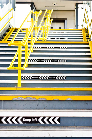 bajando escaleras: Flight of stairs in a UK train station with signs to keep left Foto de archivo