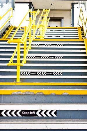 down stairs: Tramo de escaleras en una estación de ferrocarril del Reino Unido con signos de mantener izquierda