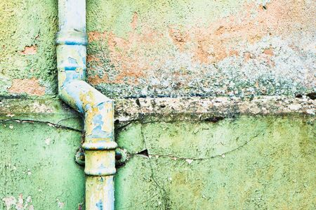 cracked wall: An old metal drainpipe on a weathered stone wall