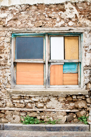 A window boarded up by wooden panels in an old house Stock Photo