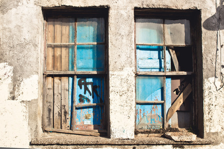repossessed: A broken, boarded up window in an old house