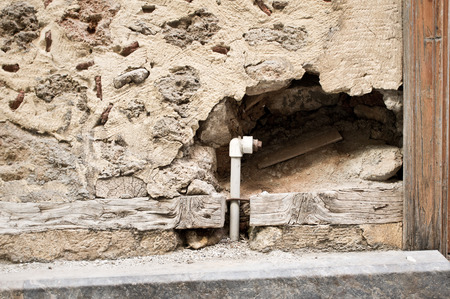 crack pipe: A hole in a stone wall with a water pipe Stock Photo