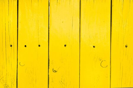 yellow paint: Part of a yellow painted fence as a background