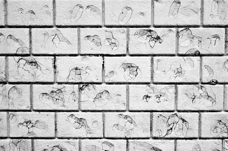 possibly: Part of a white brick wall with damage, possibly by bullets Stock Photo
