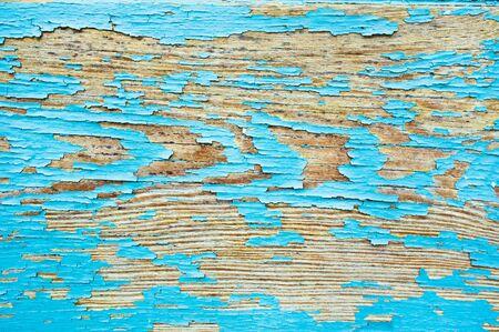 Peeling blue paint on a wood surface