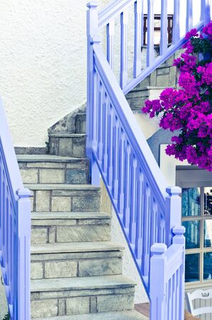 wooden railings: Blue wooden railings with stone steps outside a greek house Stock Photo