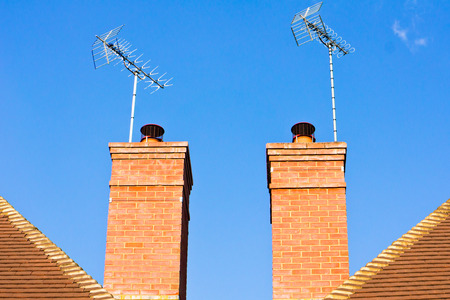 neighbouring: Chomneys on modern adjoining houses with a blue sky Stock Photo