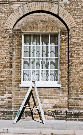 panes: A small ladder in front of the window of a town house in England