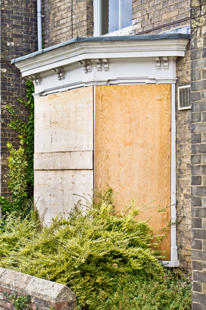 A boarded up blue front door
