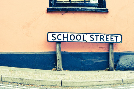 educational institution: A road sign front of a  building in the UK, with a retro filter applied Stock Photo