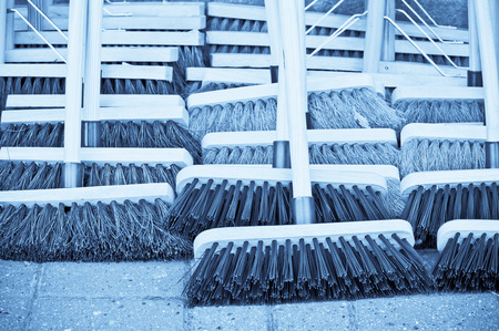 working stiff: Selection of new wooden brooms at a market, with a blue filter applied