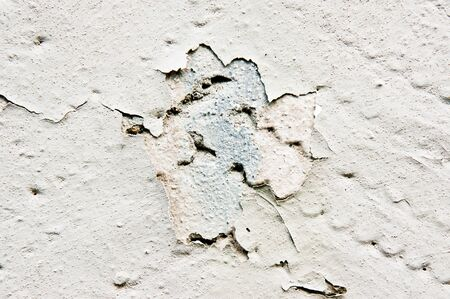 defect: A defect in a painted wall with exposed stone Stock Photo
