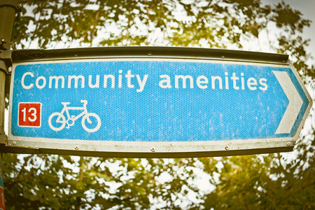 amenities: A blue sign for a cycle route to some community amenities, in the UK Stock Photo