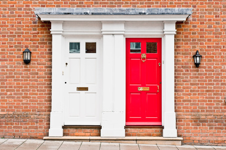 Red and white front doors in adjoining town houses Stock Photo