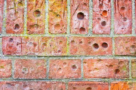 housebreaking: Part of a brick wall with holes, as a background