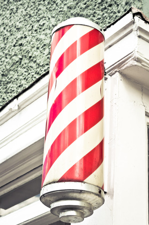 barber: A traditional red and white cylinder outside a barbers shop