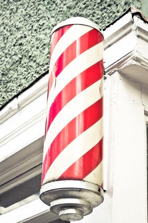 barbero: Un cilindro rojo y blanco tradicional fuera una barber�a Foto de archivo