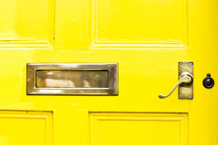 letterbox: A yellow front door with a metal letterbox and handle