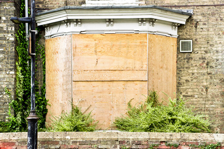A bay window on a town house which has been boarded up Stock Photo