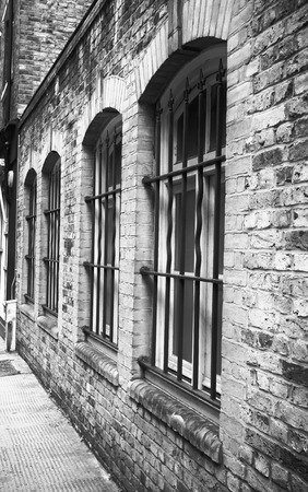 gaol: Exterior of a brick building in London with metal window bars, in black and white
