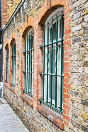 window bars: Exterior of an urban brick building in Lndonw with window bars